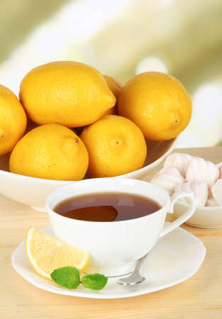 Cup of tea with lemon on table on light background photo