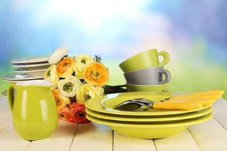 Lots beautiful dishes on wooden table on natural background photo