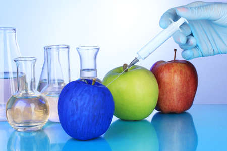 apple gmo: Injection into apple on blue background Stock Photo