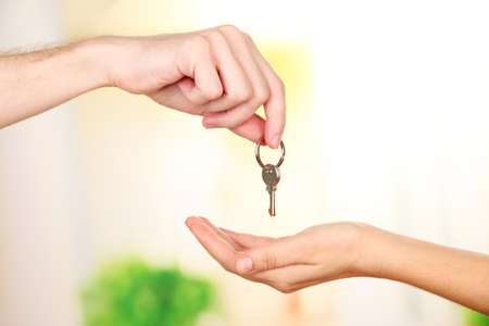 Transfer of house key, on bright background photo