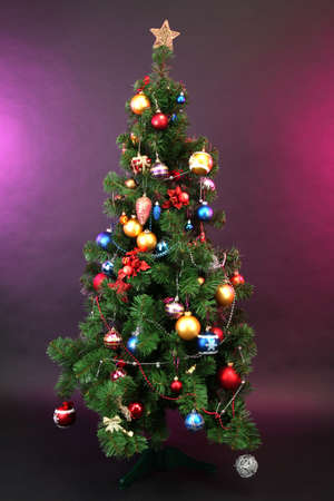 Decorated Christmas tree on dark color background photo