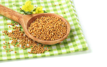 Mustard seeds in wooden spoon with mustard flower isolated on white  photo