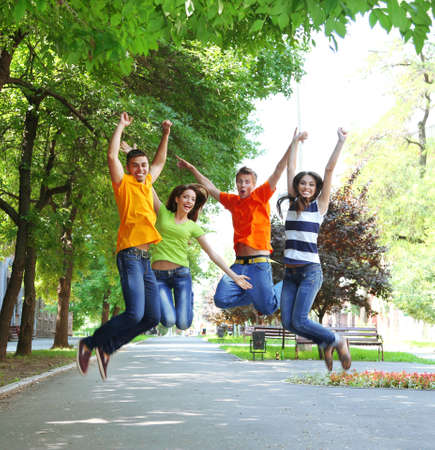 Happy group of young people jumping in park photo