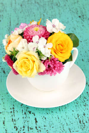 Beautiful bouquet of bright flowers in color vase,  on bright background photo