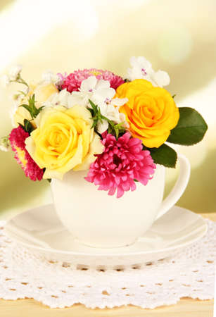 Beautiful bouquet of bright flowers in color mug, on wooden table, on bright background photo