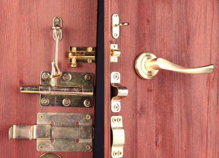 pawl: Perni metallici, serrature e ganci in porta aperta di legno close-up