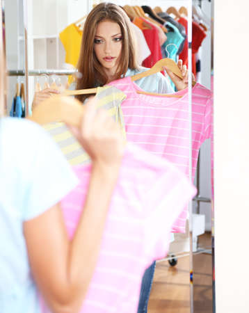 blouses: Beautiful girl choose blouses near mirror on room background Stock Photo