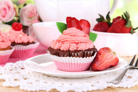 Beautiful strawberry cupcakes on dining table close-up photo