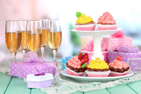Delicious beautiful  cupcakes on festive table on room background photo