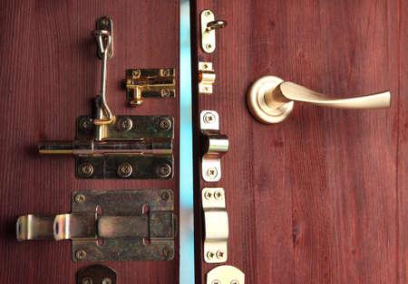 pawl: Perni metallici, serrature e ganci in porta aperta in legno close-up