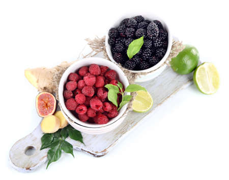 Raspberries and blackberry in small bowls on board isolated on white photo