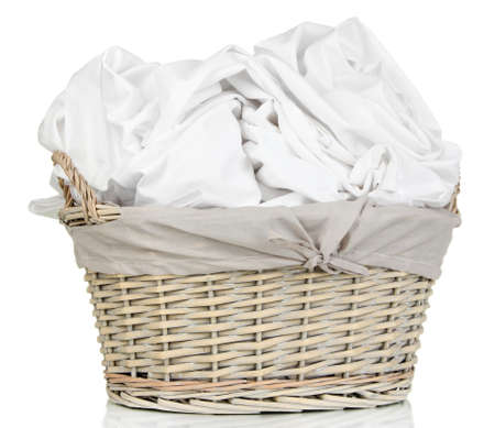 laundry room: Rumpled bedding sheets in wicker basket isolated on white