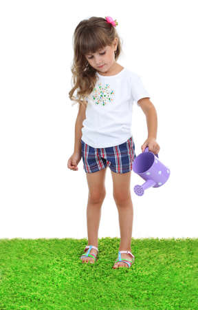 Little girl watering green grass isolated on white photo