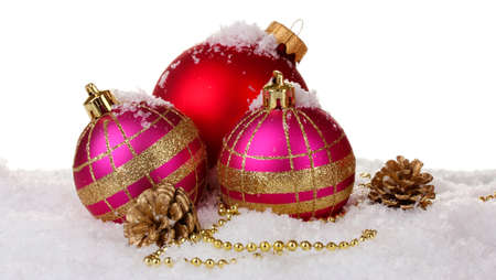beautiful pink and red Christmas balls and cones on snow isolated on white photo