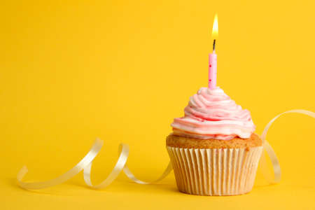 candle: tasty birthday cupcake with candle, on yellow background