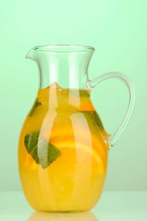 Orange lemonade in pitcher on turquoise background photo