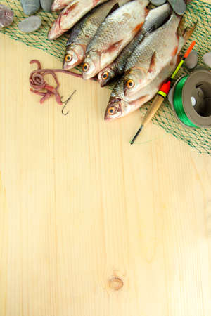 Fishes on fishing net on wooden background photo