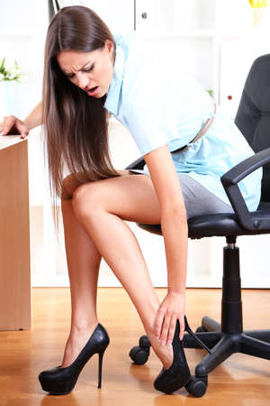 feet on desk: Young business woman in office