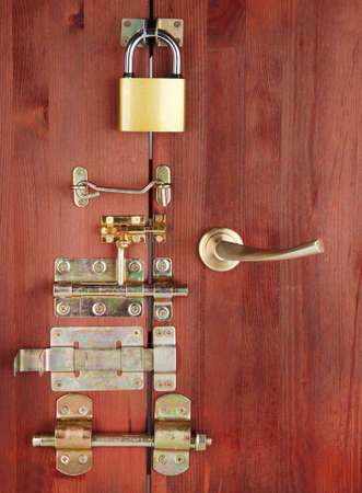 Metal bolts, latches and hooks in wooden door close-up photo