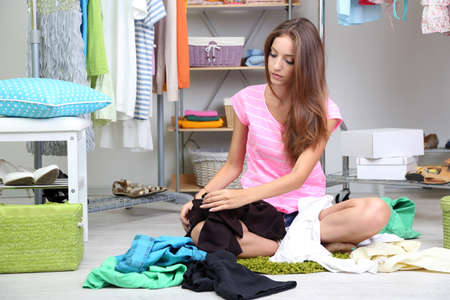 Beautiful girl chooses clothes in walk-in closet photo