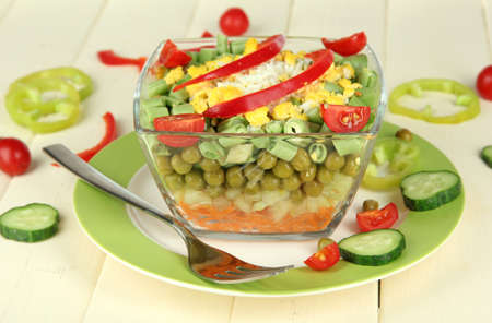 Tasty salad with fresh vegetables on wooden table photo
