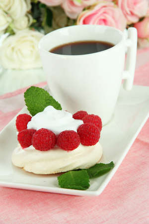 Tasty meringue cake with berries and cup of coffee photo
