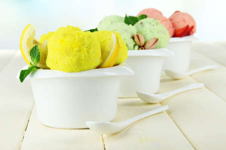 Tasty ice cream scoops in bowls, on wooden table photo