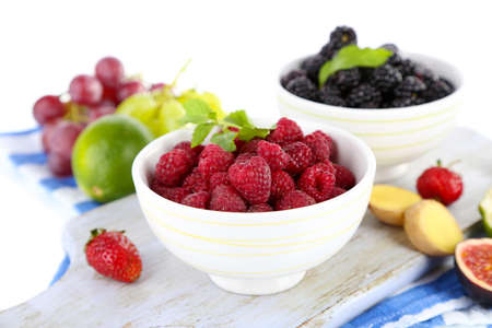 Raspberries and blackberry in small bowls on board on napkin isolated on white photo