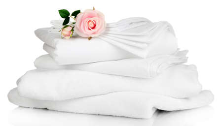 Stack of clean bedding sheets and towels isolated on white photo
