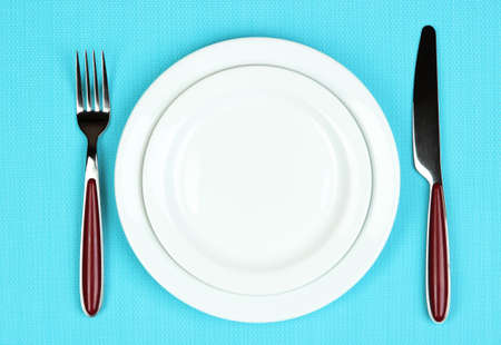 Knife, color plate and fork, on color background Stock Photo - 22282275