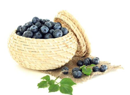 Blueberries in wooden basket on sackcloth isolated on white photo