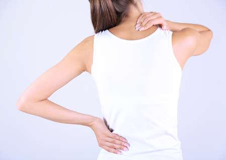 протяжение: Молодая девушка и боль в шее сером фоне Фото со стока