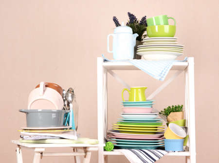 Beautiful white shelves with tableware and decor, on color wall background, close-up photo
