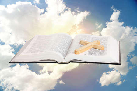 worship service: Holy Bible and wooden cross on sky background