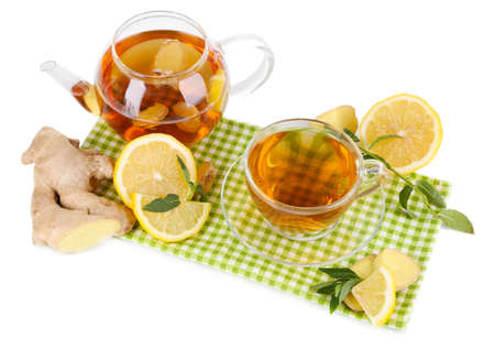 Kettle and cup of tea with ginger on napkin isolated on white photo