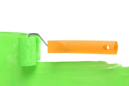 Roller brush with green paint closeup photo