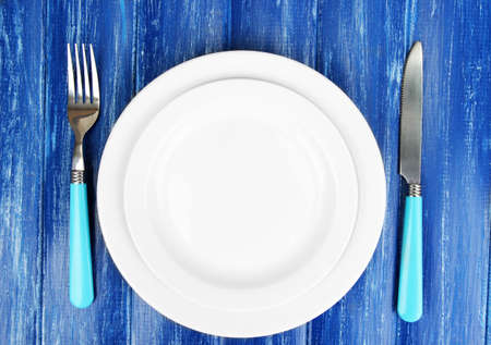 Plate and cutlery on wooden table close-up Stock Photo - 22332947