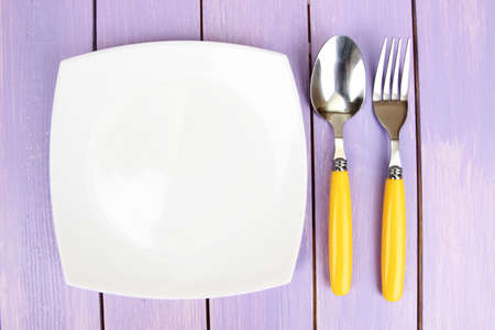 Plate and cutlery on wooden table close-up Stock Photo - 22332948