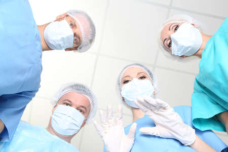 View from below of surgeons in protective work wear during\ operation