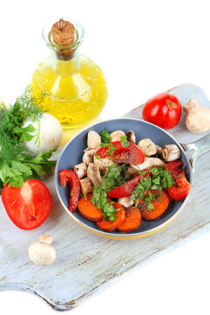 Sliced fresh vegetables in pan on wooden board isolated on white photo