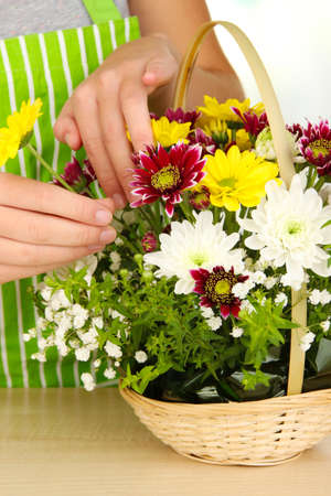 Florist makes flowers bouquet in wicker basket photo