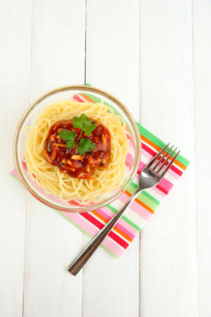 Italian spaghetti in glass bowl on wooden table photo