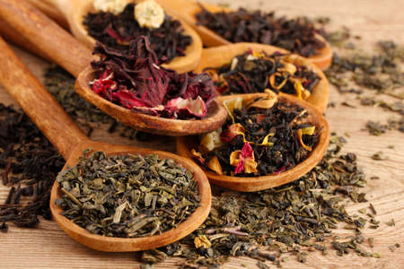 hibiscus: assortment of dry tea in spoons, on wooden background
