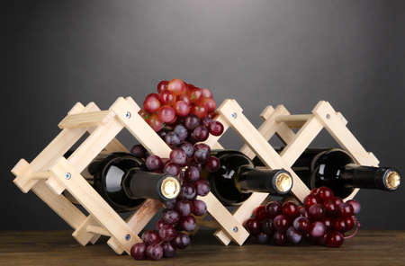 bordeau: Bottles of wine placed on wooden stand on grey background