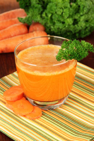 Fresh carrot juice on table close-up photo