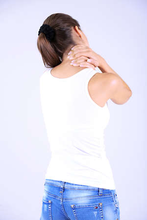 Young girl and pain in neck gray background photo