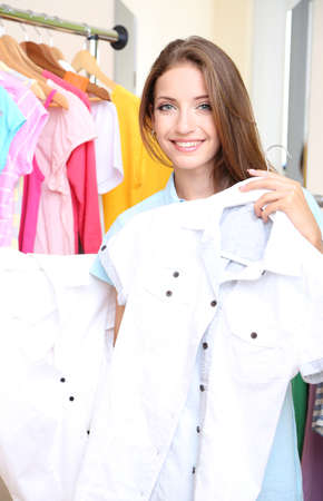 Beautiful girl chooses clothes on room background photo