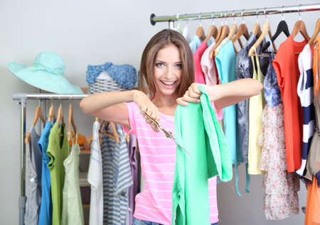 unnecessary: Beautiful girl throws out unnecessary clothes in room