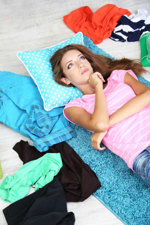 Beautiful girl lying on floor and thinking what to dress in walk-in closet photo