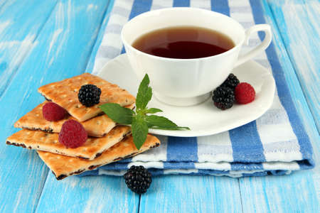 Cup of tea with cookies and berries on table close-up photo